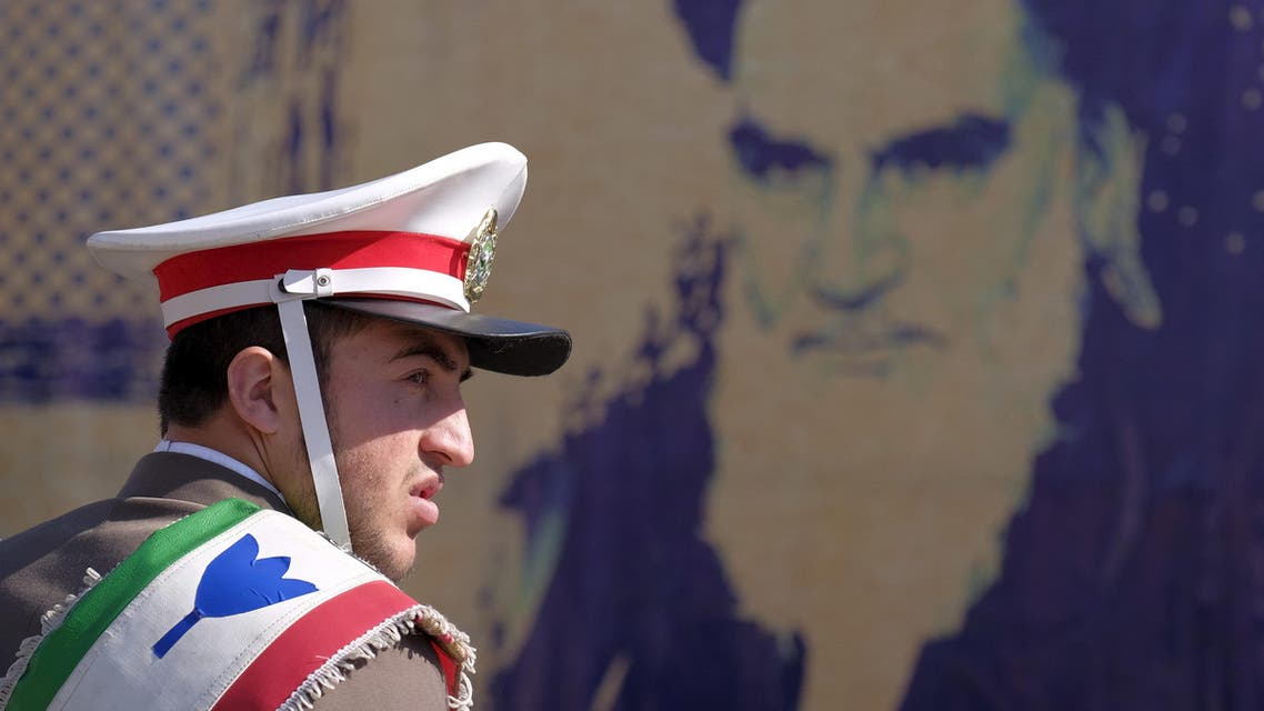An Iranian soldier stands guard in front of a picture of Iran's late leader Ayatollah Ruhollah Khomeini during the anniversary ceremony of Iran's Islamic Revolution in Behesht Zahra cemetery, south of Tehran, February 1, 2016. (Reuters)