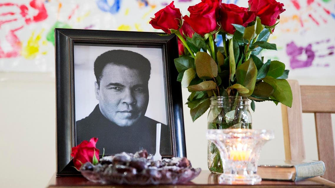 A photo of Muhammad Ali is displayed during an interfaith service at the Islamic Cultural Center of Louisville following the death of Muhammad Ali Sunday, June 5, 2016, in Louisville, Ky. Ali, the magnificent heavyweight champion whose fast fists and irrepressible personality transcended sports and captivated the world, died Friday at the age of 74. (AP)