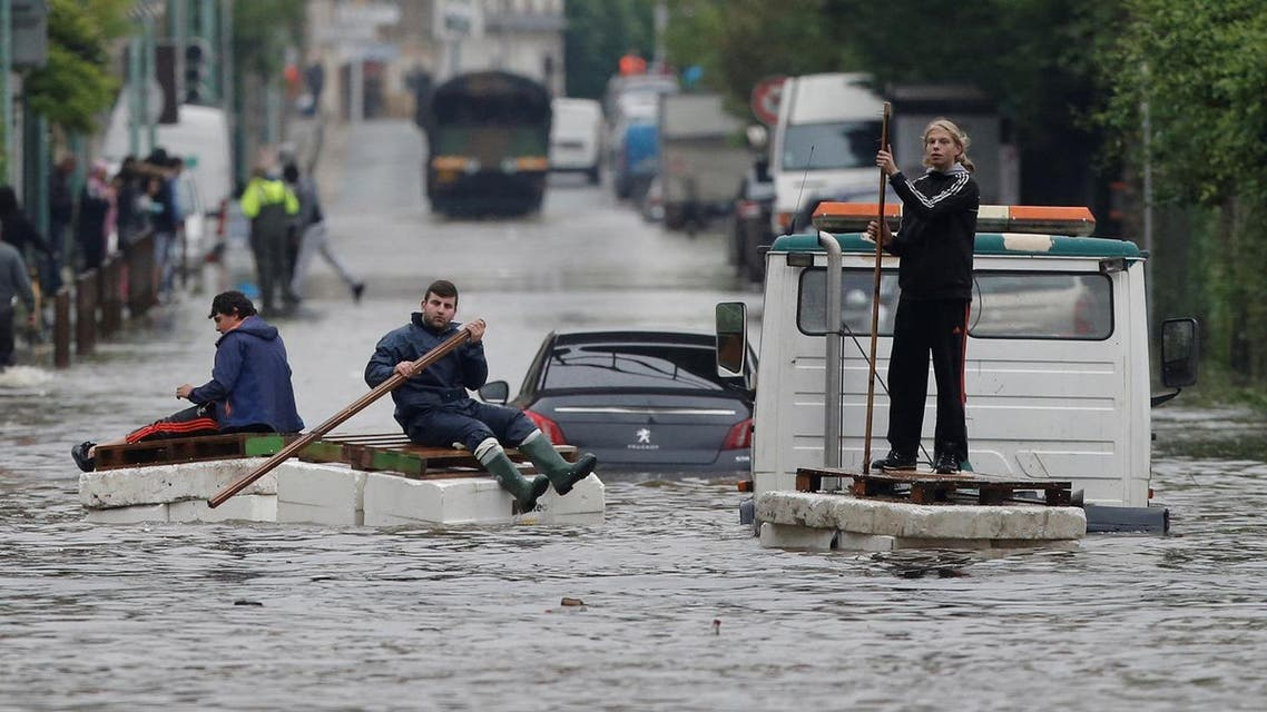 Residents who refused to be evacuated sit on makeshift boats during evacuation operations of the Villeneuve-Trillage flooded suburb in Villeneuve Saint-Georges, outside Paris, France, June 3, 2016 after days of almost non-stop rain caused flooding in the country. REUTERS
