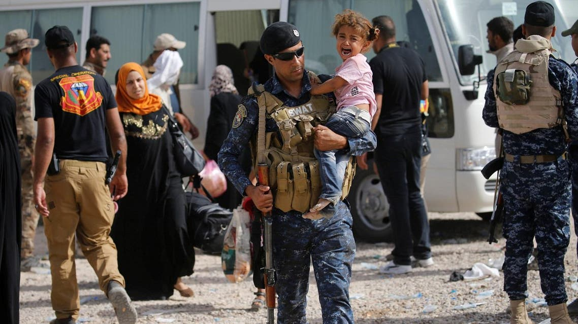 A member of the Iraqi security forces carries a child as he assists civilians, who had fled their homes due to clashes in Fallujah. (Reuters)