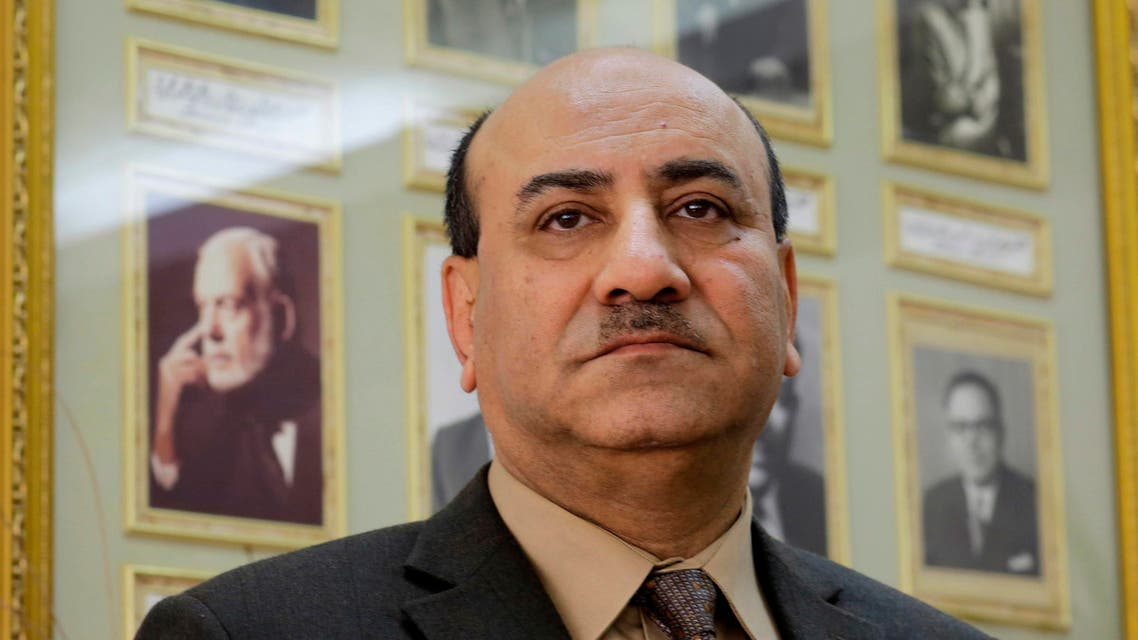 In this Tuesday, April 16, 2014 file photo, Hesham Genena, then head of Egypt's oversight body, poses for a portrait in front of pictures of his predecessors at his office in Cairo, Egypt. AP