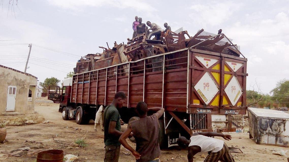 Residents evacuate in a truck metal sheets collected from houses burnt after Boko Haram attacks in Buni Yadi on May 21, 2016. (Photo: AMINU ABUBAKAR/AFP)