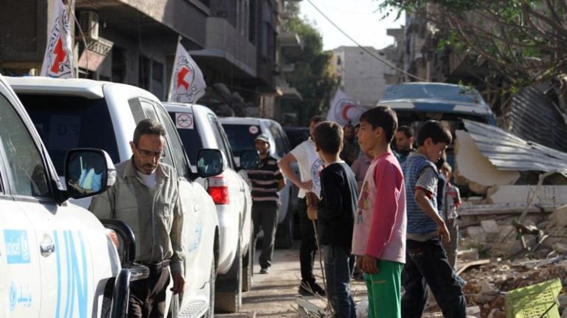 Vehicles of the International Committee of the Red Cross (ICRC), the Syrian Arab Red Crescent and the United Nations wait on a street after an aid convoy entered the rebel-held Syrian town of Daraya, southwest of the capital Damascus, on June 1, 2016. AFP