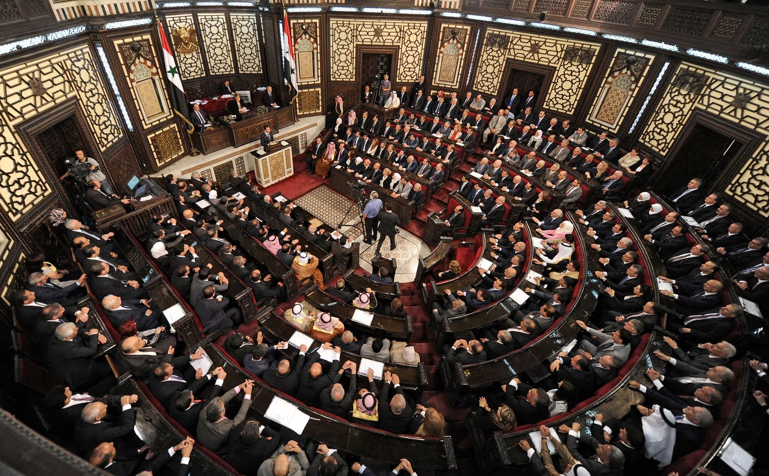 A general view shows the Syrian Parliament members listening to Syria's president Bashar al-Assad while he talks on the podium in Damascus, Syria in this handout picture provided by SANA on June 7, 2016. SANA/Handout via Reuters