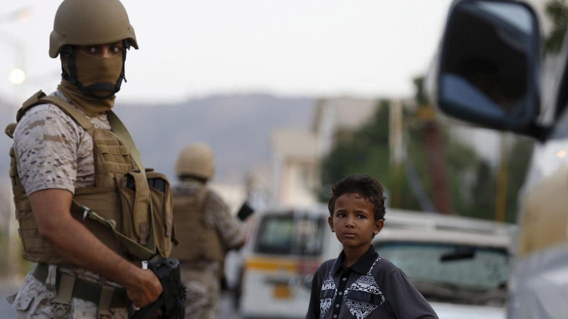 A boy stands next to soldiers from the Saudi-led coalition securing a street in Yemen's southern port city of Aden September 26, 2015. As Gulf-backed forces assemble in Marib province east of Sanaa ahead of a widely expected thrust towards the Houthi-held capital, the fate of Aden and its hinterland may offer a glimpse at whether some form of central government can be resurrected. Picture taken September 26, 2015. To match Insight YEMEN-SECURITY/ADEN REUTERS