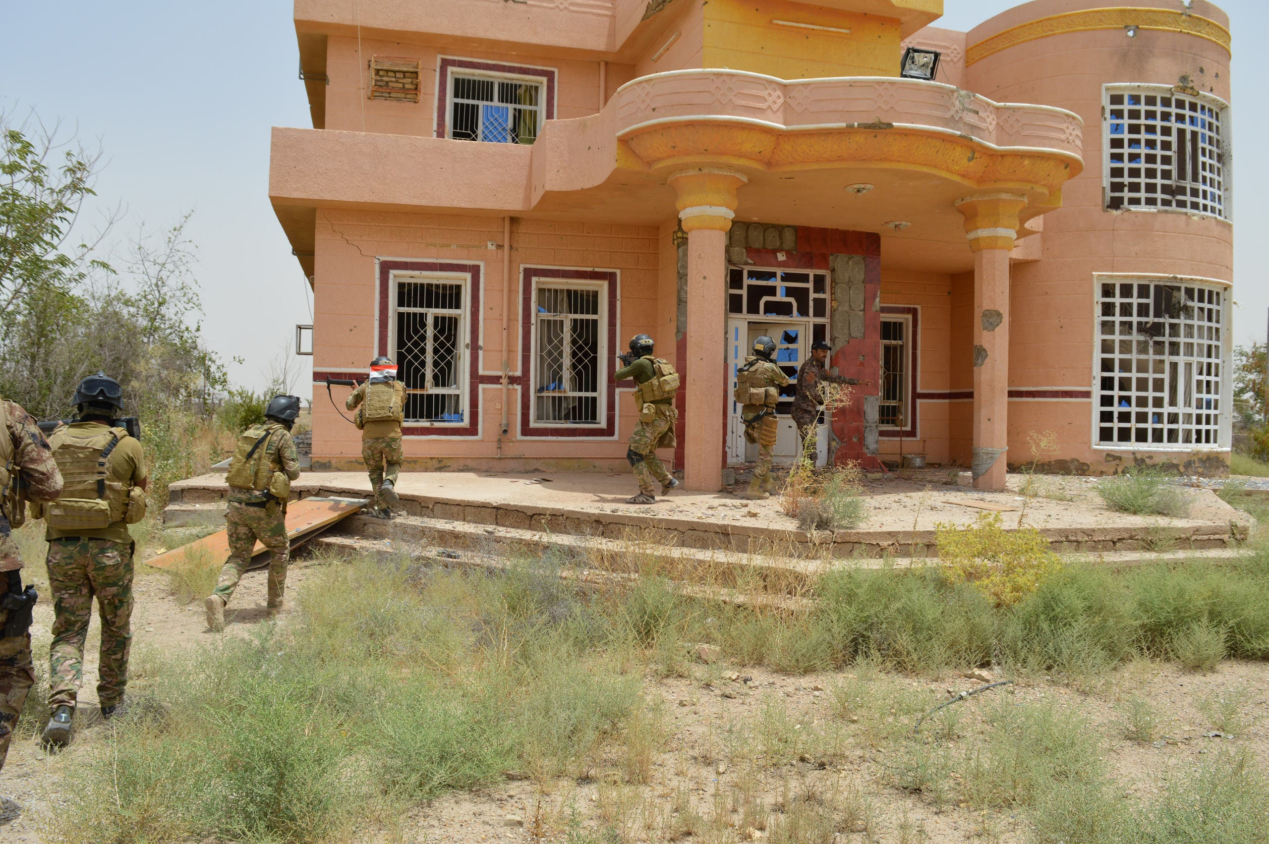 Iraqi security forces personnel walk with their weapons as they inspect a house south of Falluja, Iraq, June 6, 2016.