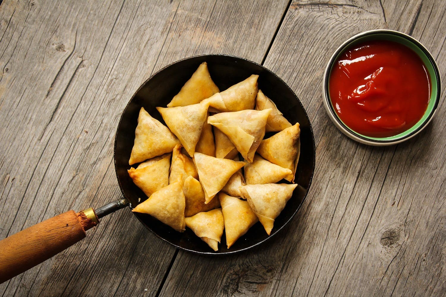 samoosa is a fried or baked dish with a savoury filling, such as spiced potatoes, onions, peas, lentils, macaroni, noodles, and/or minced meat (lamb, beef or chicken). (Shutterstock)
