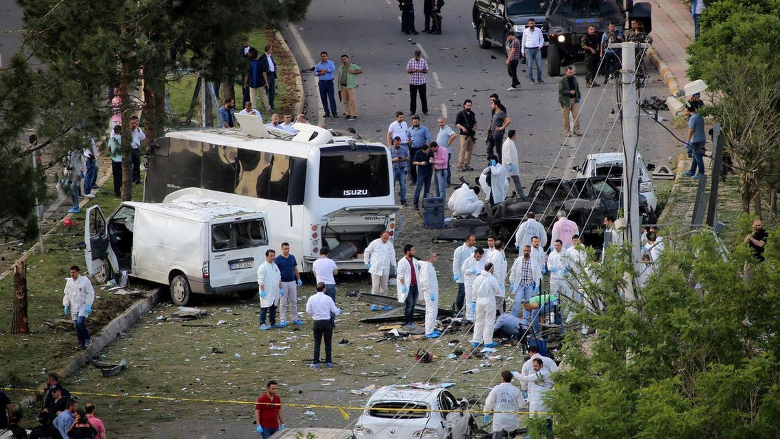 Police forensic experts examine the scene following a car bomb attack on a police vehicle in the Kurdish-dominated southeastern city of Diyarbakir, Turkey May 10, 2016. REUTERS