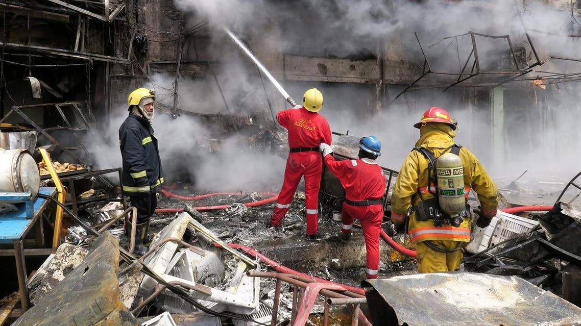 Firemen hose down a burning building at the site of car bomb attack in Baghdad al-Jadeeda. (Reuters)