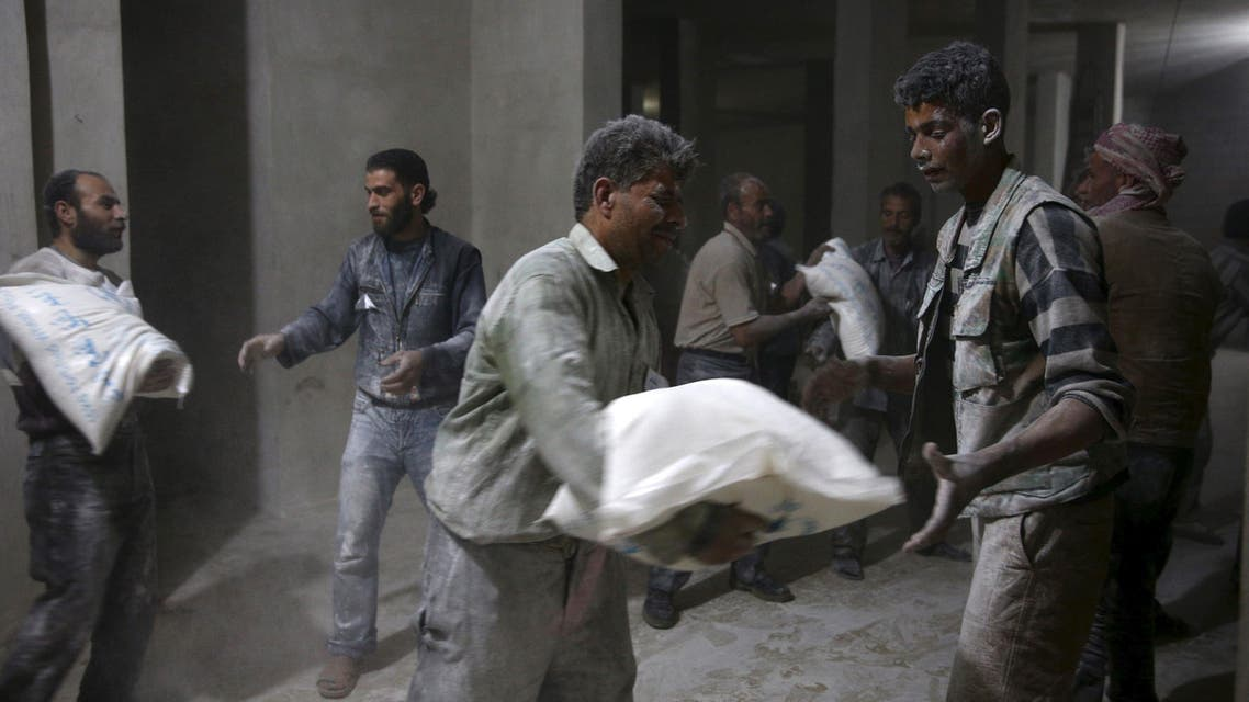 Men store bags of flour unloaded from a Red Crescent aid convoy in the rebel held besieged town.