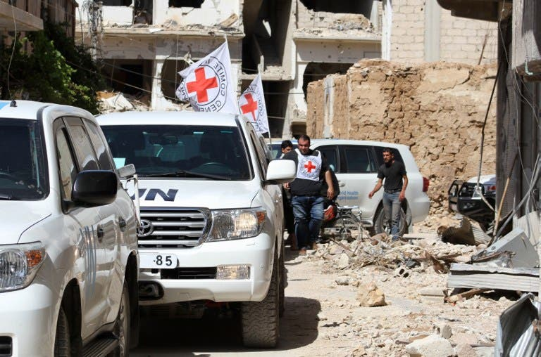 Vehicles of the International Committee of the Red Cross (ICRC) and the United Nations wait on a street after an aid convoy entered the rebel-held Syrian town of Daraya, southwest of the capital Damascus, on June 1, 2016. (AFP)