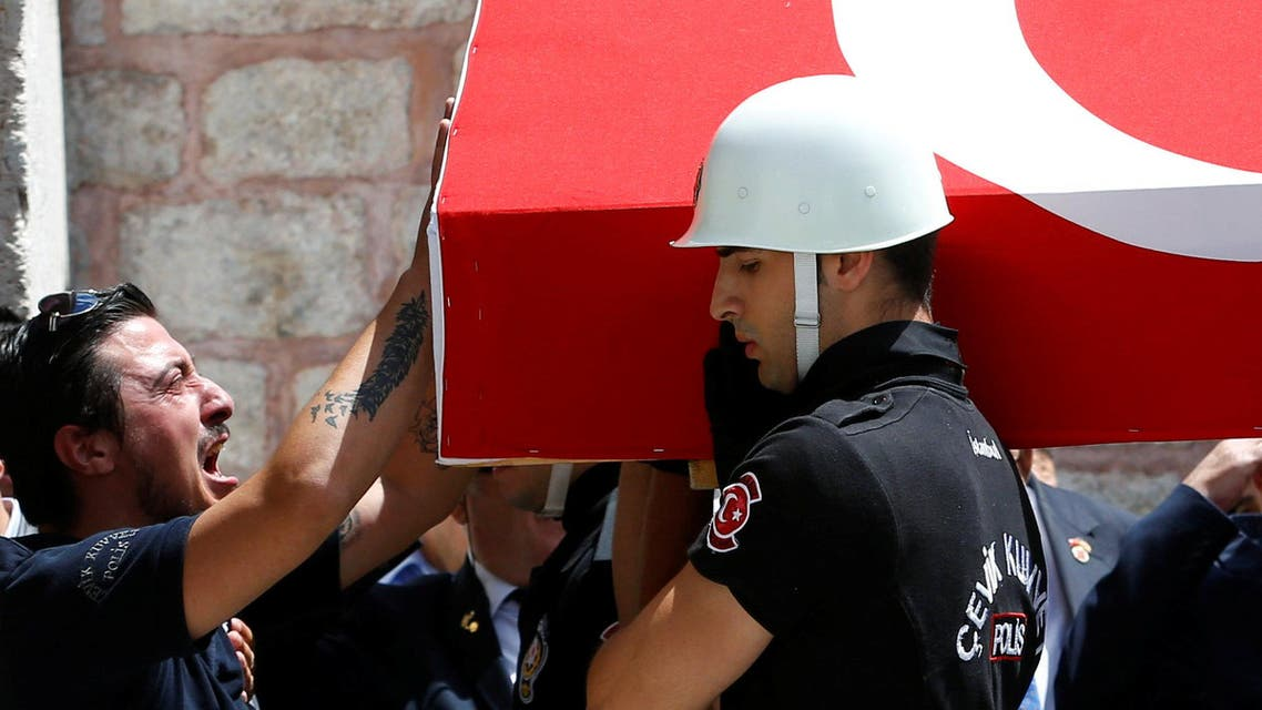 A comrade mourns as honour guards carry the coffin of police officer Karagozlu who was killed in Tuesday's car bomb attack on a police bus, during a funeral ceremony at Fatih mosque in Istanbul. (Reuters)
