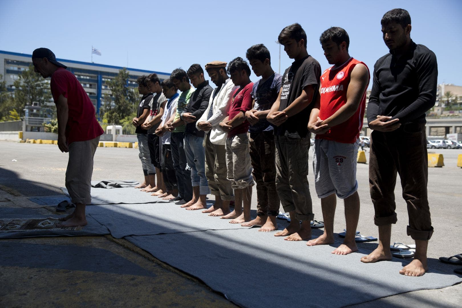 Afghan migrants stranded in Greece, pray on a dock at the port of Piraeus, near Athens on the first day of the holy fasting month of Ramadan. (AP)