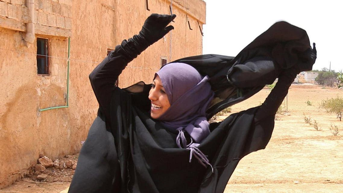 A woman removes a Niqab she was wearing in her village after Syria Democratic Forces (SDF) took control of it, on the outskirts of Manbij city, Aleppo province, Syria June 9, 2016.  (Reuters)