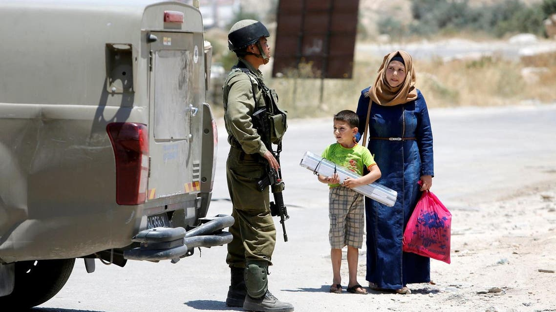 An Israeli soldier stops a Palestinian woman and her son at the entrance of Yatta near the West Bank city of Hebron June 9, 2016. REUTERS