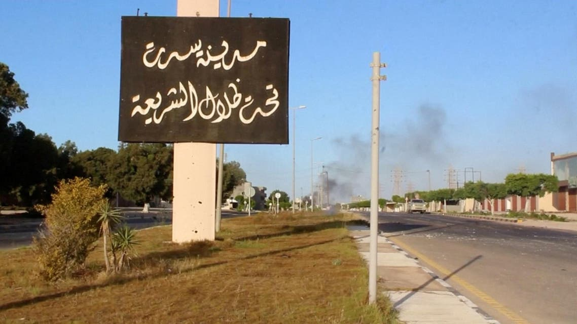 "A sign which reads in Arabic, ""The city of Sirte, under the shadow of Sharia"" is seen as smoke rises in the background. (Reuters)"