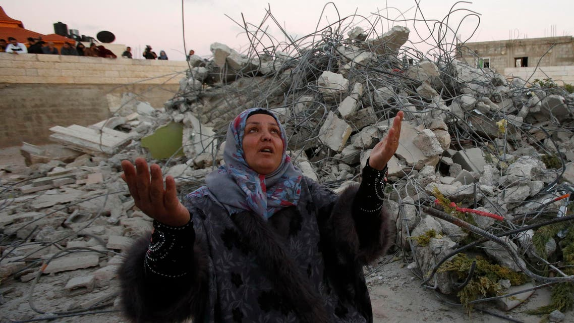 Maha the mother of 15-year old Palestinian teenager Murad Ideis, who was accused of stabbing to death a 38-year old Israeli nurse in an attack in the Israeli Otniel settlement in January 2016, reacts next to the rubble of her home after Israeli security force demolished the building in the West Bank village of Beit Amra, south of Hebron on June 11, 2016. (AFP)