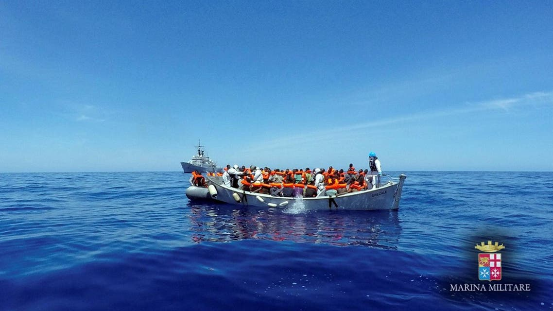 Migrants sit in their boat during a rescue operation by Italian navy ship Grecale (unseen) off the coast of Sicily, Italy, in this handout picture courtesy of the Italian Marina Militare released on May 6 2016. Marina Militare/Handout via REUTERS