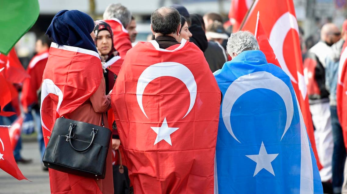 """Pro-Turkish protestors wearing Turkish flags take part in a demonstration in Hamburg, April 10, 2016. A 'Peace March for Turkey and the EU', organized by """"Avrupa Yeni Turkler Komitesi"""" (AYTK, European New Turks Committee) was held in Hamburg and other German cities on Sunday. Counter-demonstrations by Kurdish and leftist groups were simultaneously held to demonstrate against what they say are the nationalist-Islamist policies of Turkish President Tayyip Erdogan. REUTERS"""