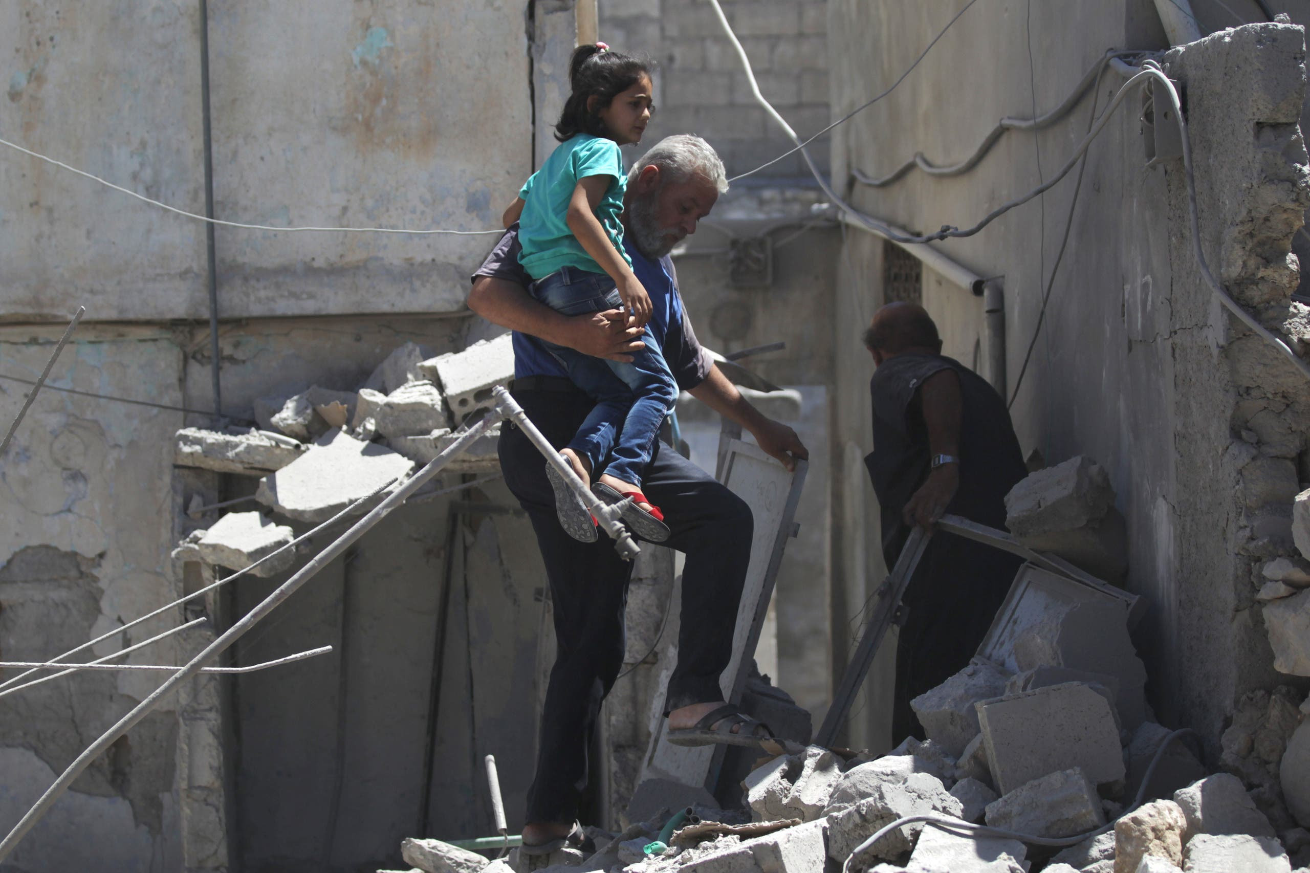 A man carries a girl as he makes his way through the rubble at a site hit by airstrike in the rebel-controlled area of Maaret al-Numan town in Idlib province, Syria, June 12, 2016. REUTERS