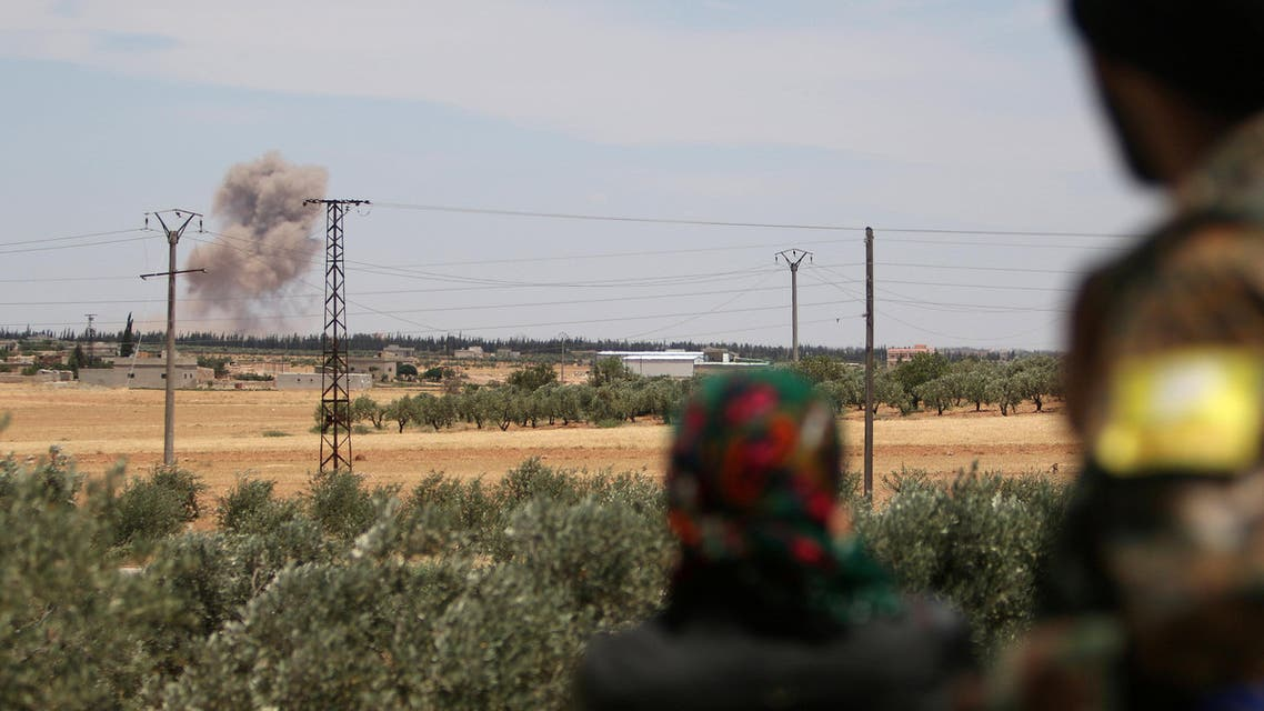 Fighters of the Syria Democratic Forces (SDF) look at a smoke rising from what they say were U.S.-led air strikes on positions controlled by Islamic State militants, in the western rural area of Manbij, in Aleppo Governorate, Syria June 11, 2016. REUTERS