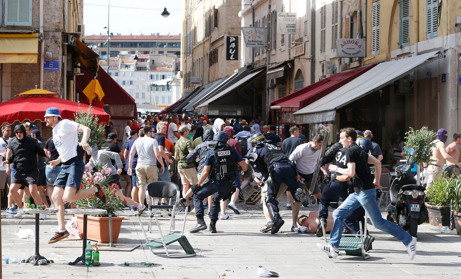 French police officers charge soccer supporters during clashes in downtown Marseille, France, Saturday, June 11, 2016. Riot police have thrown tear gas canisters at soccer fans Saturday in Marseille's Old Port in a third straight day of violence in the city. (AP)