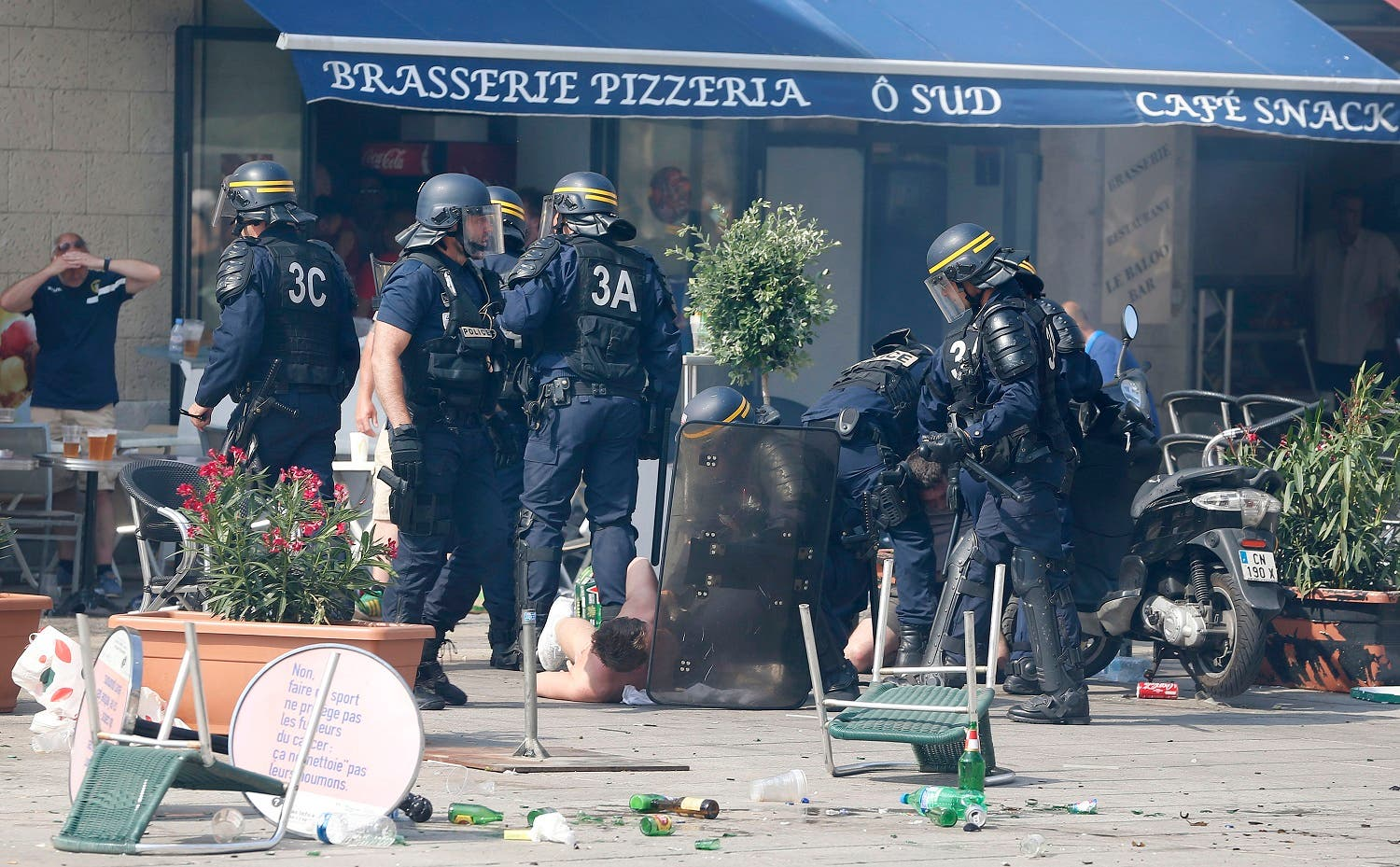 French police officers apprehend soccer supporters during clashes in downtown Marseille, France, Saturday, June 11, 2016. Riot police have thrown tear gas canisters at soccer fans Saturday in Marseille's Old Port in a third straight day of violence in the city. (AP