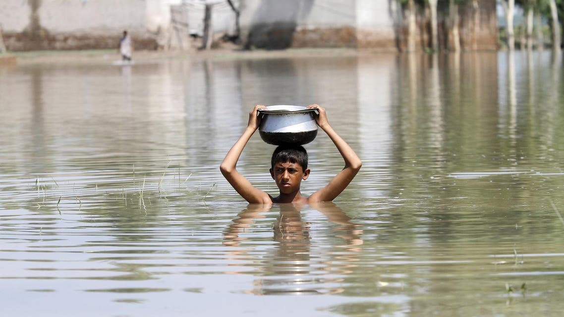 A boy carries a pot on his head as he moves through floodwaters at Camp Koruna Akbar in the Pura area of Nowshera District, northwestern Pakistan, August 4, 2015. Flash flooding caused by torrential monsoon rains affected hundreds of thousands of people, according to aid agencies, with further monsoon downpours expected in the coming days. REUTERS/Fayaz Aziz