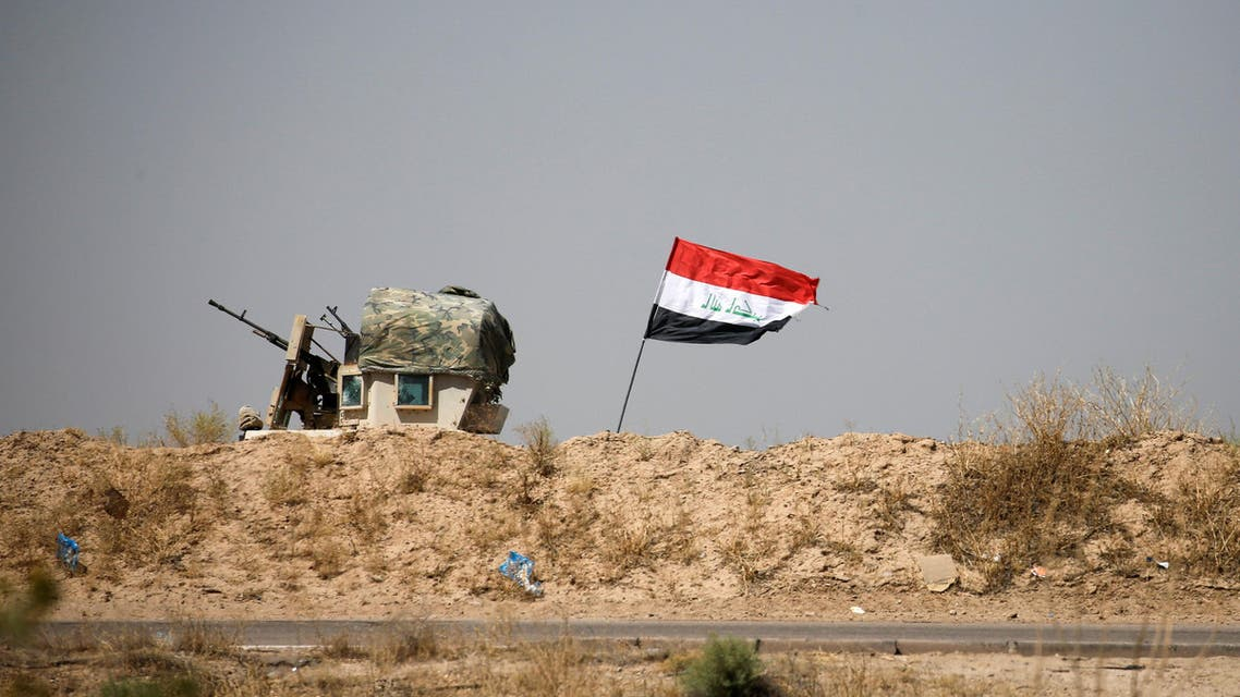 A military vehicle of the Iraqi security forces is seen next to an Iraqi flag in Falluja, Iraq, June 13, 2016. reuters