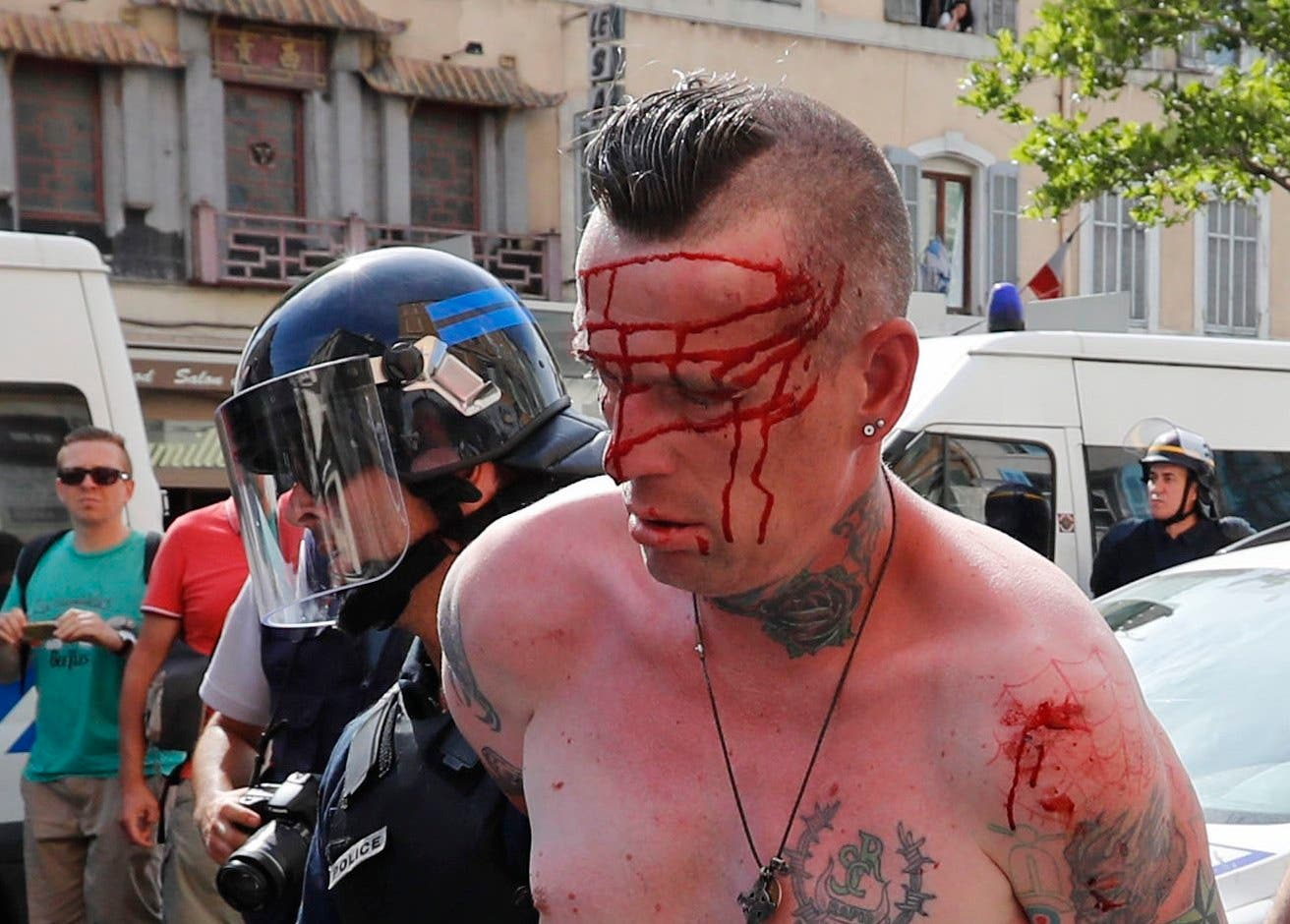 A man is arrested by police officers in downtown Marseille, France. (AP)