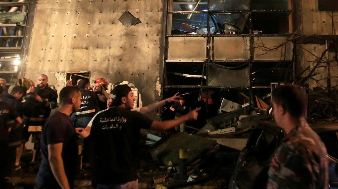 Civil defense members and policemen inspect the site of an explosion at Blom Bank in Beirut. (Reuters)