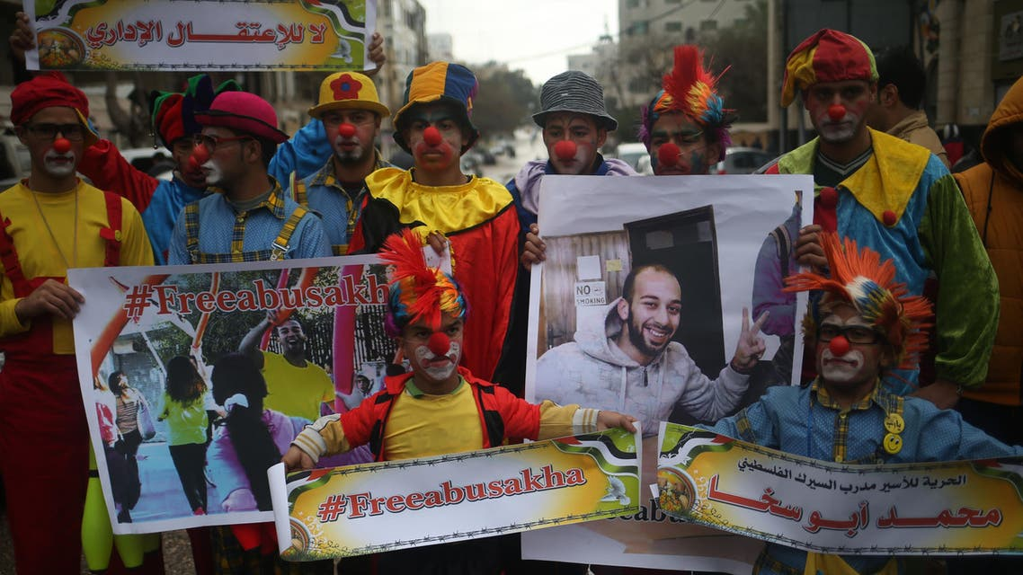 Palestinian clowns hold portraits of their colleague Mohammed Abu Sakha, who is imprisoned in an Israeli jail, as they demonstrate in solidarity with him on February 8, 2016 in Gaza City. MOHAMMED ABED / AFP