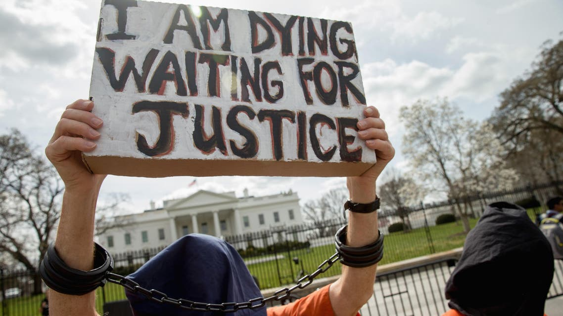 A man dressed as a detainee holds a sign calling attention to the detainees at Guantanamo Bay during a demonstration outside the White House in Washington, Friday, March 11, 2016. (aP)