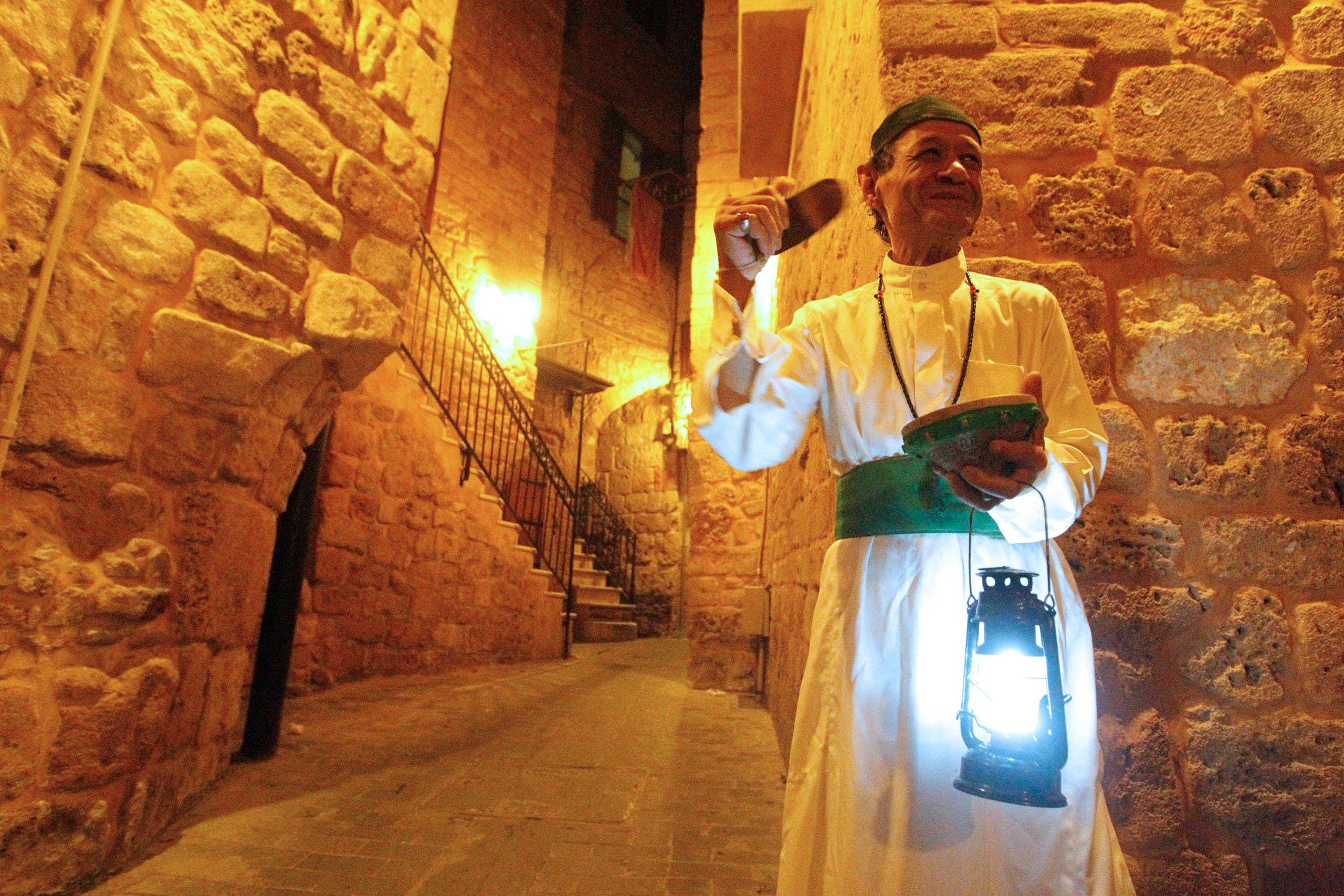 A Mesaharaty, or dawn awakener, strikes his drum to wake observant Muslims for their overnight 'sahur', last meal, before the day's fast during Ramadan in Sidon's Old City in south Lebanon just before dawn July 12, 2013. (Reuters)