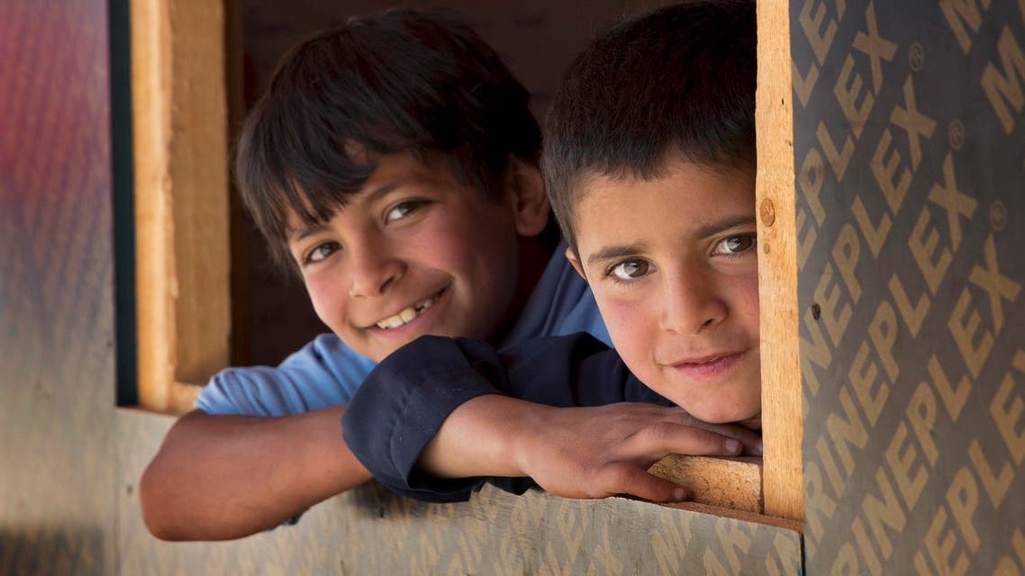Syrian refugee children pose for a picture from the window of their classroom at a non-formal school, built by the NGO Kayany Foundation, where only Syrian students are enrolled, in the town of Saadnayel, in the Bekaa valley, Lebanon, Thursday, May 12, 2016. (AP)