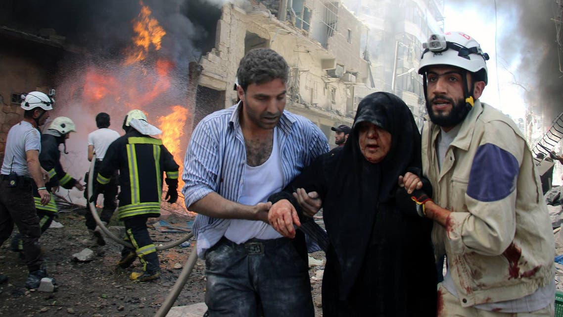 Syrian civil defense workers, right, help an injured woman after warplanes attacked a street, in Aleppo, Syria. (AP)