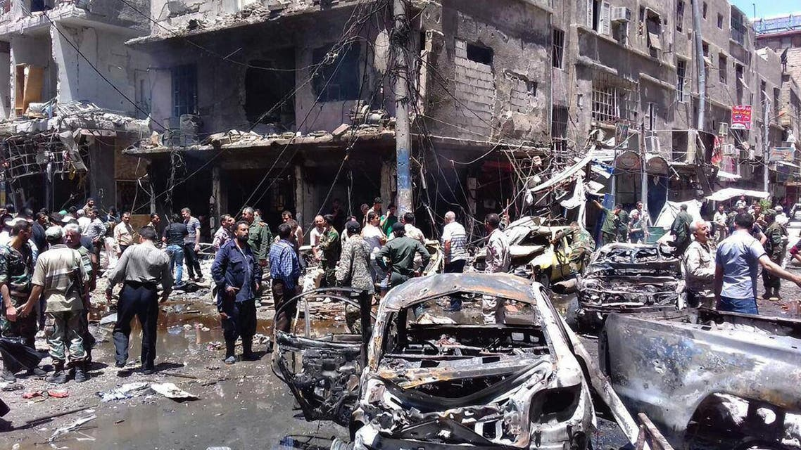 In this photo released by the Syrian official news agency SANA, Syrians gather around damaged buildings after a bombing attack at the Sayyida Zeinab suburb, Damascus, Syria, Saturday, June 11, 2016. (AP)