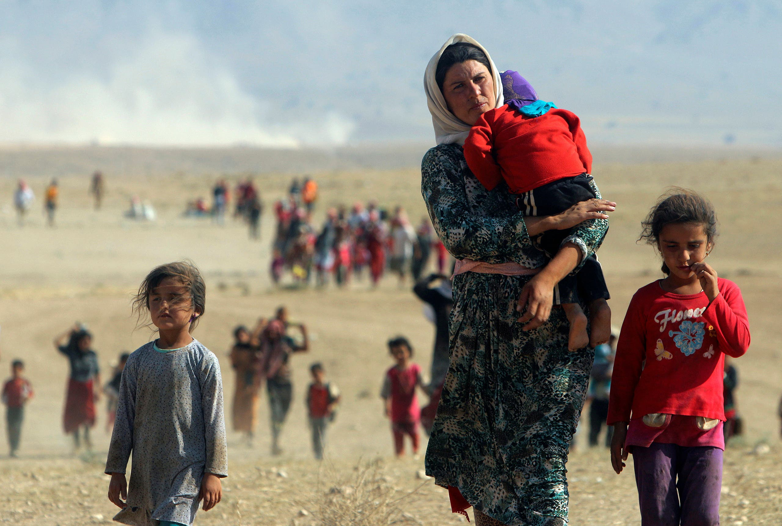 Displaced people from the minority Yazidi sect, fleeing violence from forces loyal to ISIS in Sinjar town, walk towards the Syrian border on the outskirts of Sinjar mountain near the Syrian border town of Elierbeh of Al-Hasakah Governorate in this August 11, 2014. (File photo: Reuters)