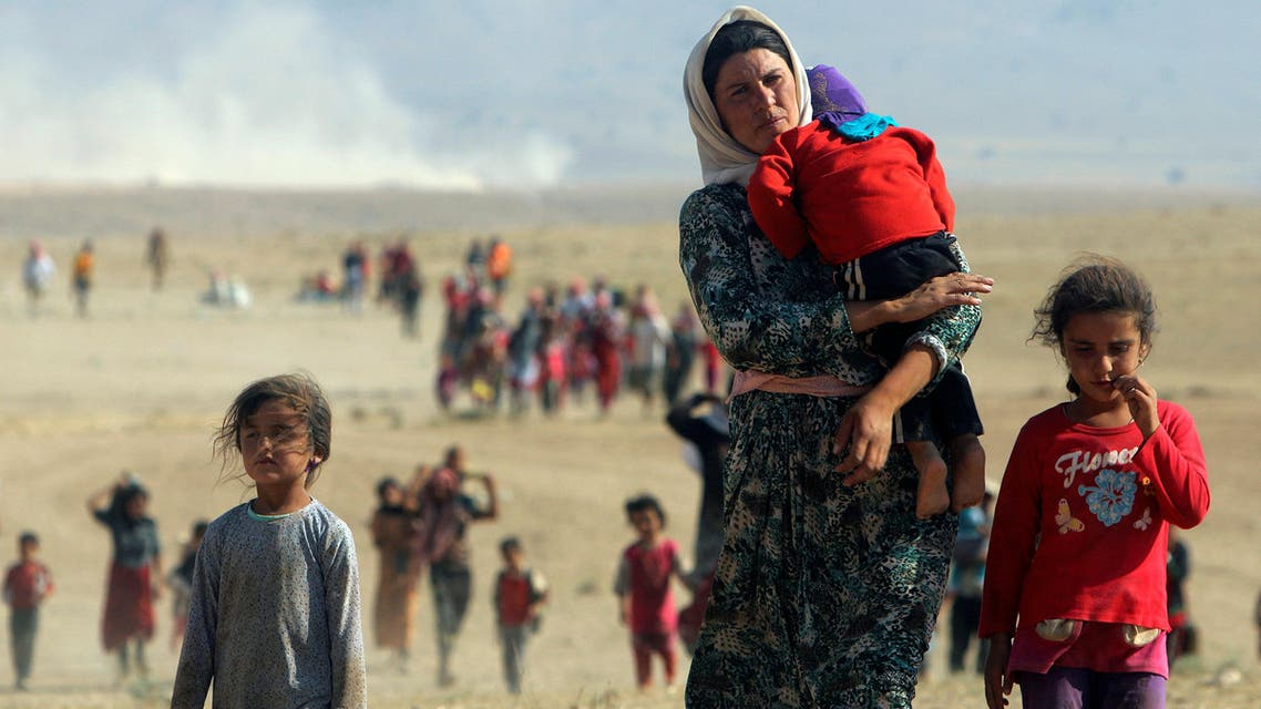 Displaced people from the minority Yazidi sect, fleeing violence from forces loyal to the Islamic State in Sinjar town, walk towards the Syrian border on the outskirts of Sinjar mountain near the Syrian border town of Elierbeh of Al-Hasakah Governorate in this August 11, 2014. reuters
