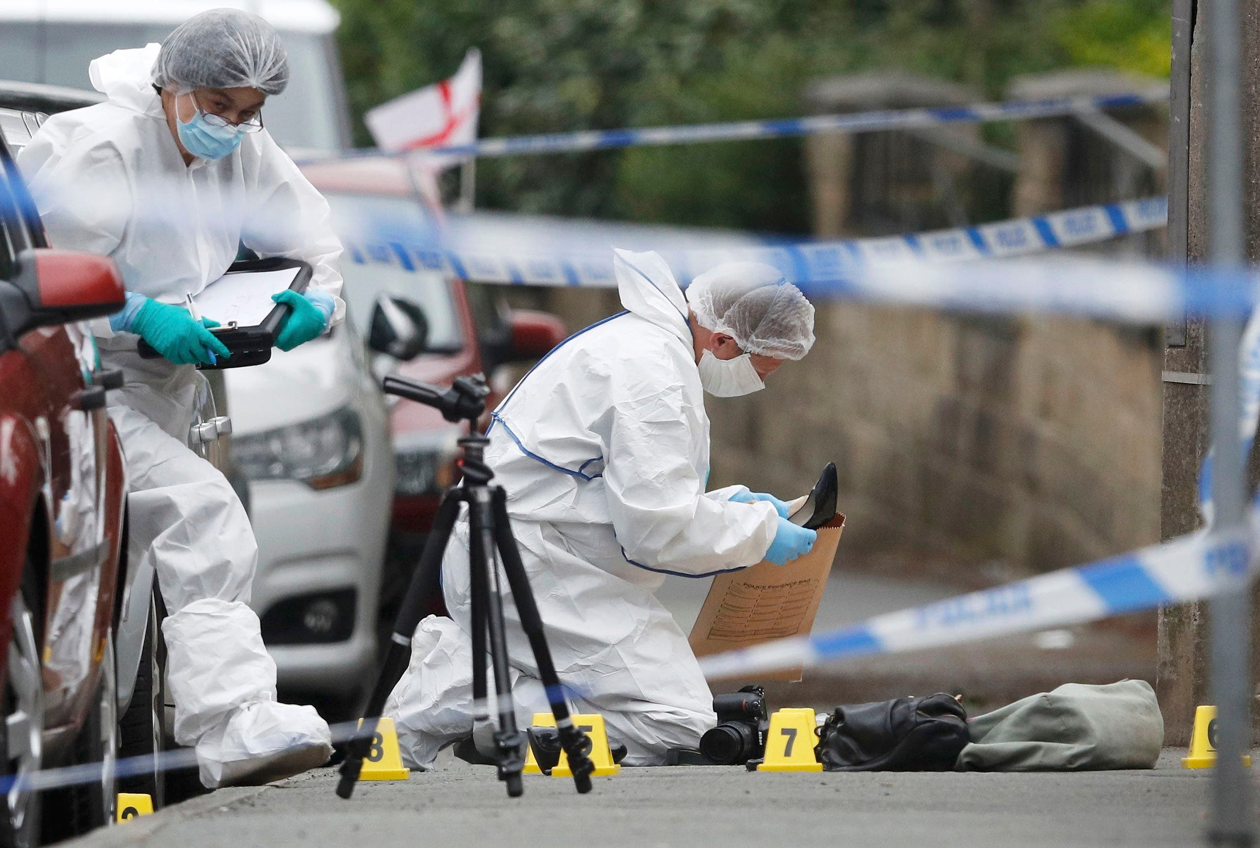 Forensics police officers collect a woman's shoes on the ground behind a police cordon in Birstall near Leeds, June 16, 2016. reuters