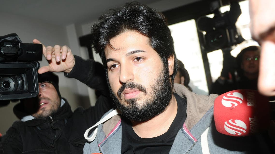 Detained Azerbaijani businessman Reza Zarrab (C) is surrounded by journalists as he arrives at a police center in Istanbul on December 17 ,2013. afp