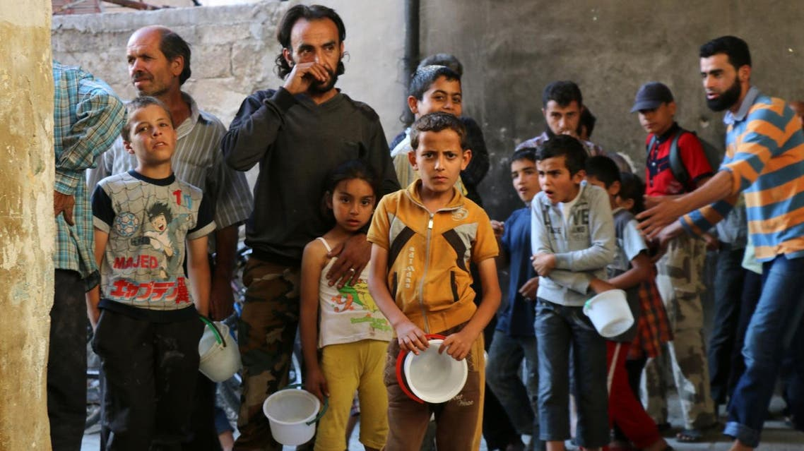 """Syrians line-up waiting to receive meals distributed by the """"Syria charity"""" NGO to impoverished families during the Muslim holy fasting month of Ramadan. (AFP)"""