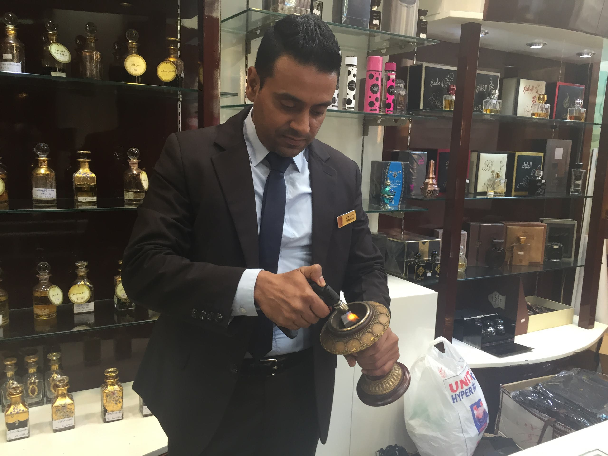 Siraj Hassan Gawai, a branch manager and sales supervisor at Arabian Oud in Dubai demonstrates the burning of the oud. (Ismaeel Naar/Al Arabiya English)