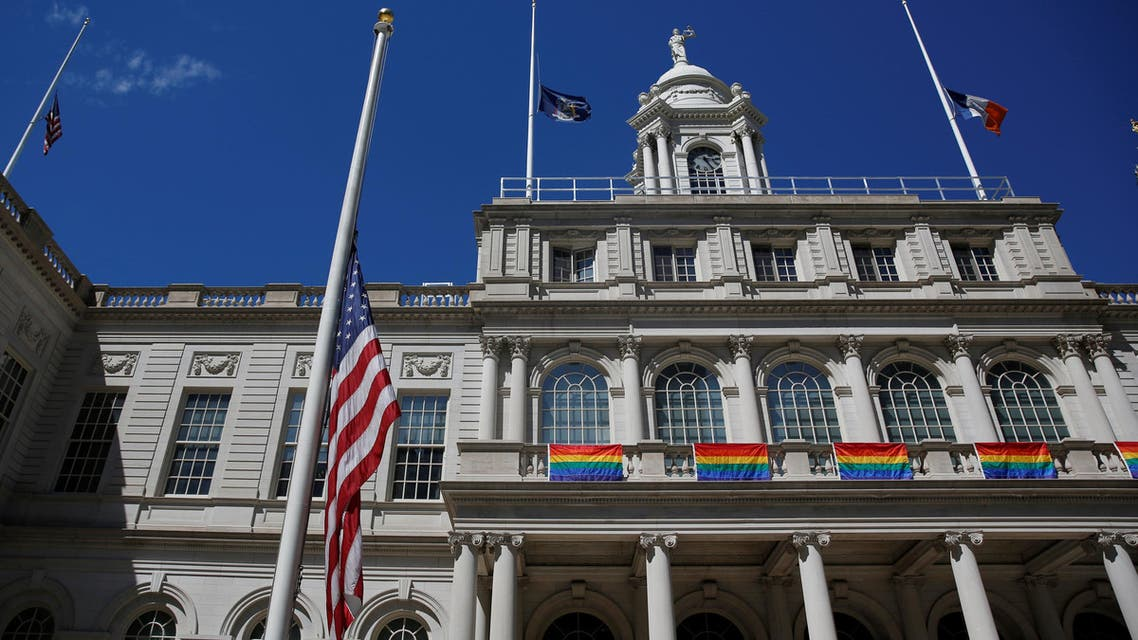 Flags are seen flying at half mast honoring the victims of the Orlando massacre at New York's City Hall in Manhattan, U.S., June 13, 2016. REUTERS