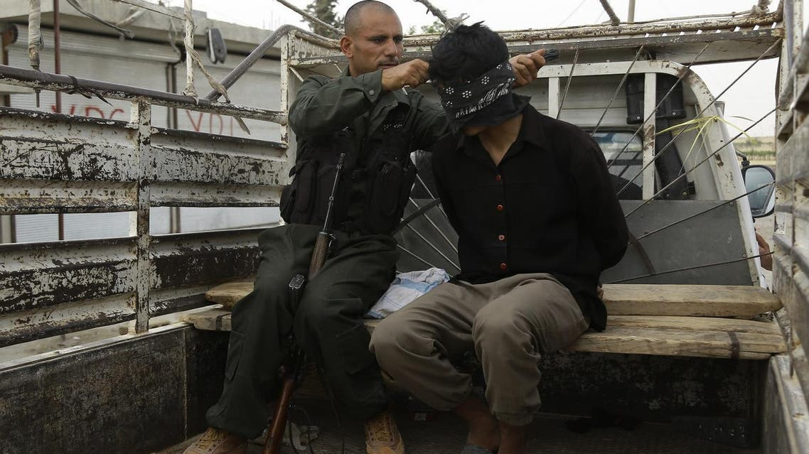 A fighter of Syria's Manbij military council (L) blindfolds a reported Islamic State (IS) group fighter sitting in the back of a pickup truck on June 15, 2016 on the outskirts of the northern Syrian town of Manbij, which is held by jihadists of the Islamic State (IS) group, during an operation to try to retake the town. Hundreds of civilians escaped the IS stronghold of Manbij in nearby Aleppo province on June 12, helped by a US-backed Kurdish-Arab alliance surrounding the town. Tens of thousands had been trapped inside Manbij after the alliance encircled the town on June 10 in a major blow to the jihadist group controlling it.  DELIL SOULEIMAN / AFP