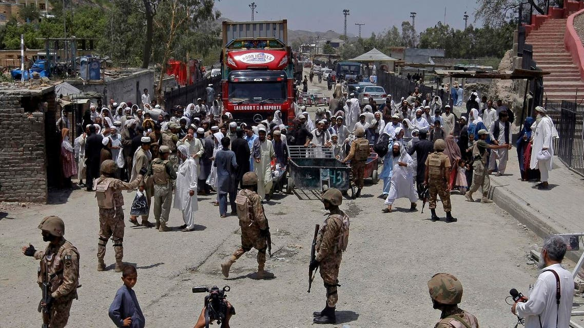 Pakistani troops stand guard while Afghans wait to cross through the Torkham border crossing with Afghanistan in Torkham, Pakistan, Saturday, June 18, 2016 (Photo: AP)