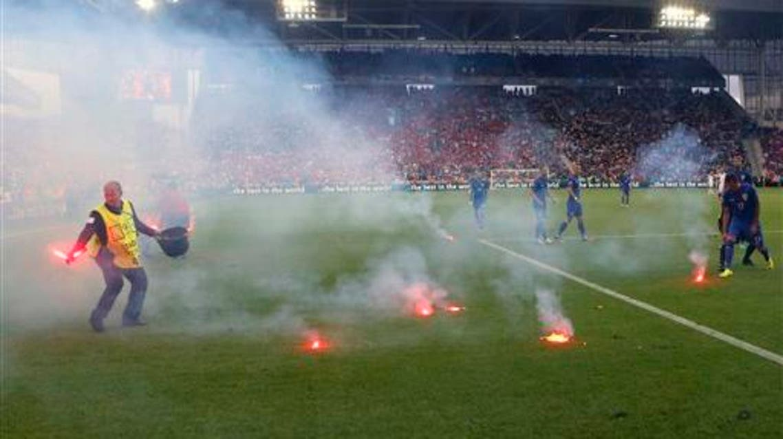 Flares are thrown onto the pitch during the Euro 2016 Group D soccer match between the Czech Republic and Croatia at the Geoffroy Guichard stadium in Saint-Etienne, France, Friday, June 17, 2016. AP