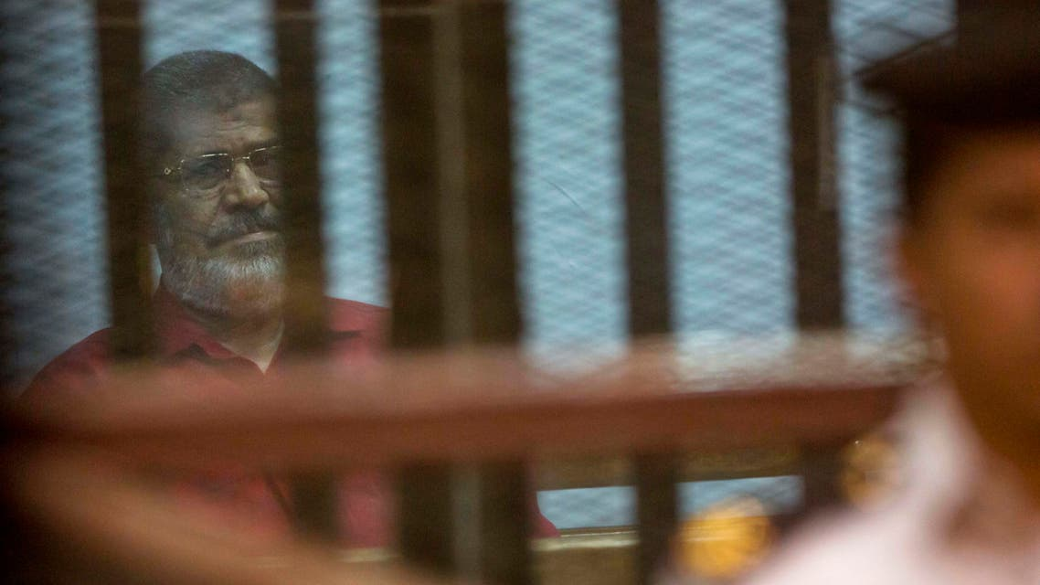 Ousted Egyptian President Mohammed Morsi, wearing a red jumpsuit that designates he has been sentenced to death, is guarded by a policeman as he sits inside a defendants cage in a makeshift courtroom at the national police academy, in an eastern suburb of Cairo, Saturday, April 23, 2016. AP