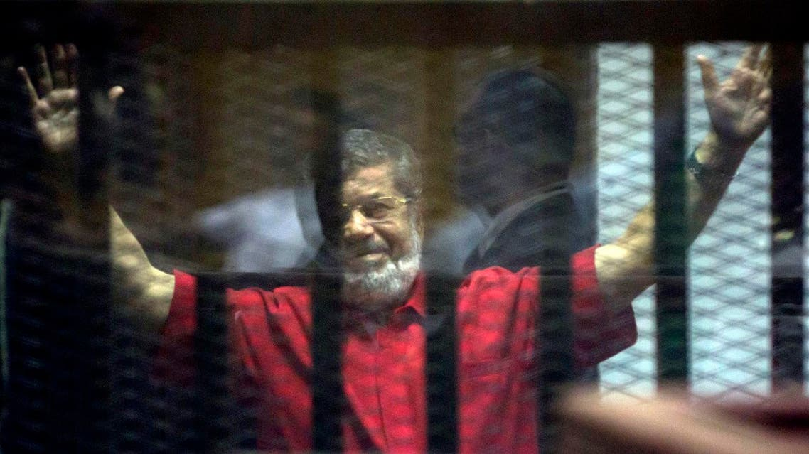 Former Egyptian President Mohammed Morsi, wearing a red jumpsuit that designates he has been sentenced to death, raises his hands inside a defendants cage in a makeshift courtroom at the national police academy, in an eastern suburb of Cairo, Egypt, Saturday, June 18, 2016. (AP)