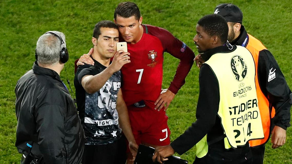 Portugal's Cristiano Ronaldo poses for a selfie with a man who invaded the pitch at the end of the Euro 2016 Group F soccer match between Portugal and Austria at the Parc des Princes stadium in Paris, France, Saturday, June 18, 2016. (AP)